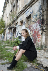 Teen girl sits in poor and dangerous district