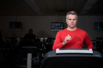 Mature man running at gym
