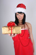 Beautiful brunette woman in santa hat holding golden present