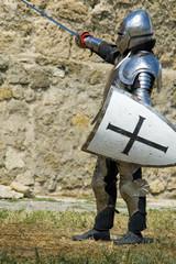 Medieval european knights fighting near citadel wall