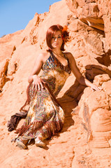 Beautiful woman laying on a rock in the desert