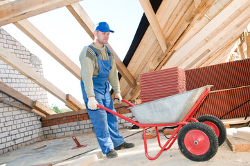 worker roofer and wheel barrow with clay tile