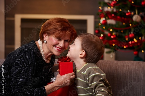 Small boy getting christmas present from grandmother