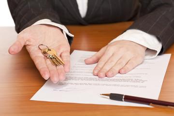 Frau übergibt Schlüssel und Mietvertrag am Schreibtisch