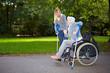 Frau hilft alter Frau auf Krücken