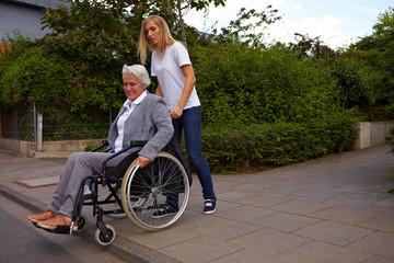 Frau hilft Rollstuhlfahrerin über Stufe