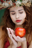 attractive girl in natural wreath with apple