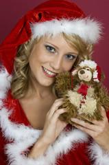 Frau mit Santa Claus Kleidung und Teddy.