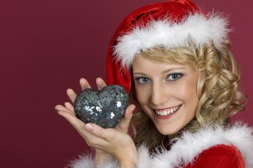Frau im Weihnachtskleidung mit einem Herz.