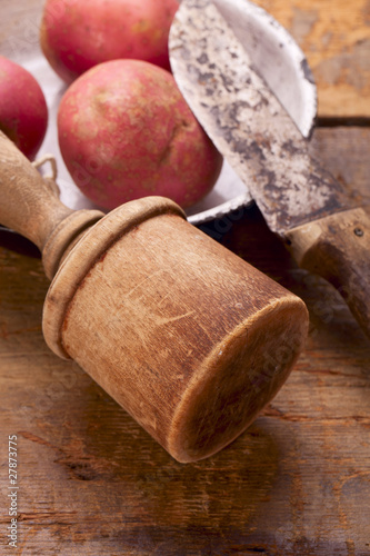 retro potato masher and knife on old wooden table with potato