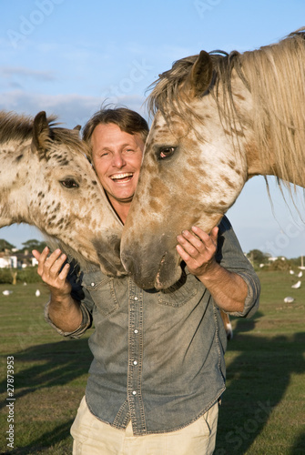 A happy smiling man petting his horses
