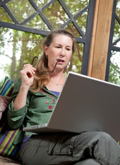 Serious Mature Woman at Home at Laptop Computer