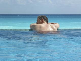 Mann im Swimmingpool mit Meerblick