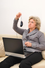 middle-aged woman with a laptop looking surptizingly at computer