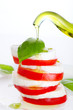 Fresh salad with mozzarella, tomato and basil with olive oil pou