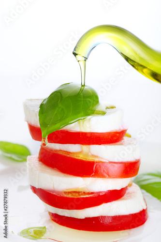 Fresh salad with mozzarella, tomato and basil with olive oil pou