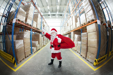 Santa Claus + sack , ringing in a bell in storehouse + gifts