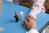 Closeup of doctor's hand holding patient's hand with medicine on table
