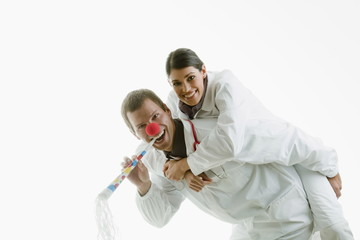Male and female doctors playing with party toys