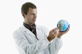 Doctor holding stethoscope to globe