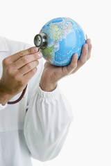 Doctor's hands holding stethoscope to globe
