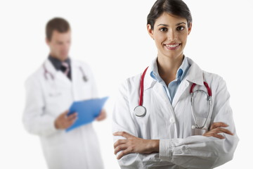 Doctor with arms folded and doctor reading medical chart