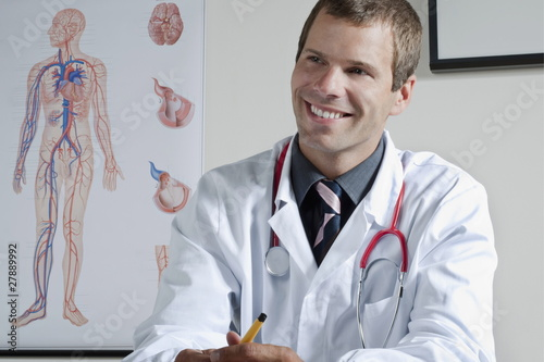 Doctor in his office with circulatory system chart on wall