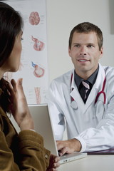 Doctor at laptop with patient in office