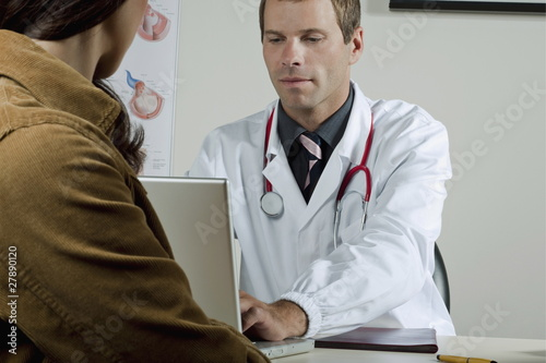 Doctor on laptop with patient in office