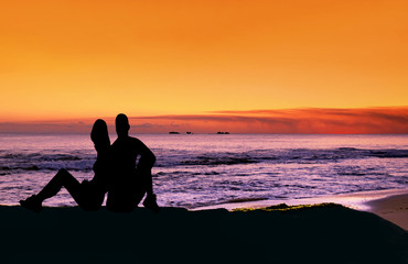 Couple sitting at the beach at sunset