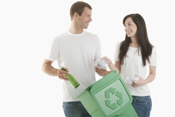 Couple throwing glass and plastic bottles in the recycling bin