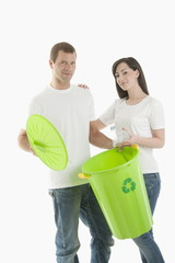 Couple throwing plastic bottle in the recycling bin