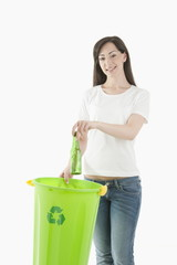 Young woman throwing glass bottle in the recycling bin