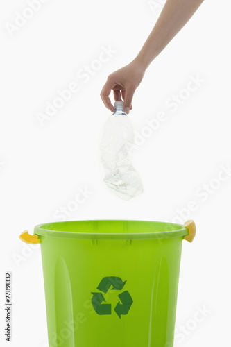 Young woman's arm throwing plastic bottle in the recycling bin