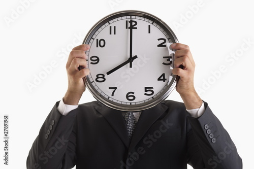 Man holding clock in front of his face