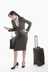 Young woman in suit with wheeled suitcase screaming at phone