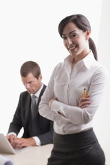 Woman with man in background at laptop