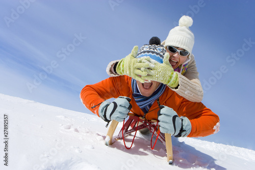 Woman covering husband's eyes as they ride through snow on sled together