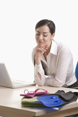 Woman sitting at desk looking at beach gear