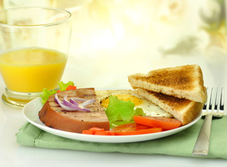 Sliced grilled ham with egg ,toasts ,vegetables and  juice