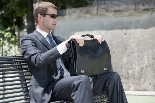 Businessman in suit with briefcase sitting on bench