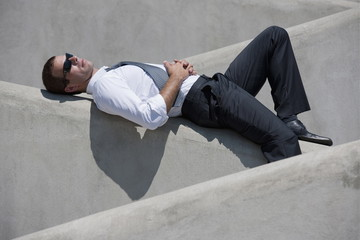 Man with tie and sunglasses lying down on wall