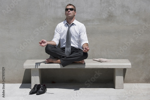 Barefoot businessman sitting on bench enjoying the sun