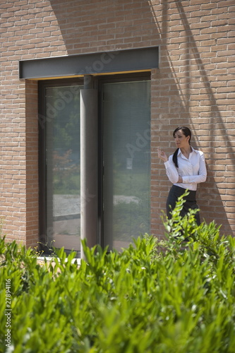 Young woman smoking a cigarette outside building