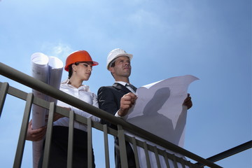 Professionals holding plans at construction site