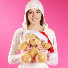A young brunette girl in a hoodie is holding a teddy bear