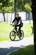 Businessman in suit riding bike