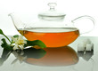 glass teapot with green tea and lemon tree flowers