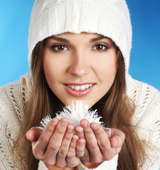 Portrait of a young brunette girl holding a snowflake