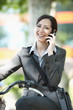 Woman in suit on bicycle talking on cellphone